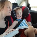 Mother reading a book to son in the carsdvwrv