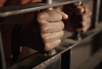 prisoner-holding-the-bars-of-his-cell-racial-profiling-of-young-black-men-in-america_t20_b8LekVsdfwefqef