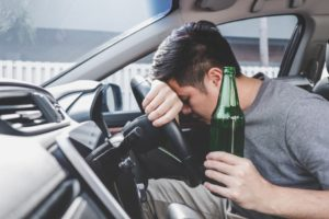 young-asian-man-drives-a-car-with-drunk-a-bottle-of-beer-and-fall-asleep-behind-the-wheel-of-a-car_t20_8d16pBSFGWEF
