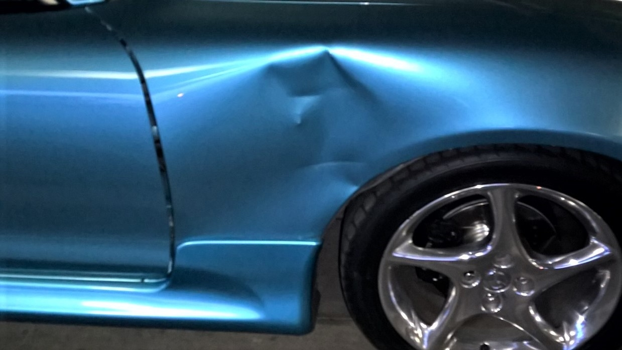 a-beautiful-blue-sports-car-a-beautiful-blue-sports-car-with-a-fender-bender-taking-the-car-to-the_t20_P1KvaNDFBD