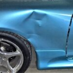 a-beautiful-blue-sports-car-a-beautiful-blue-sports-car-with-a-fender-bender-taking-the-car-to-the_t20_9860vy